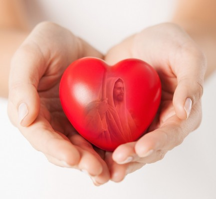 health, medicine and charity concept - close up of female hands with small red heart